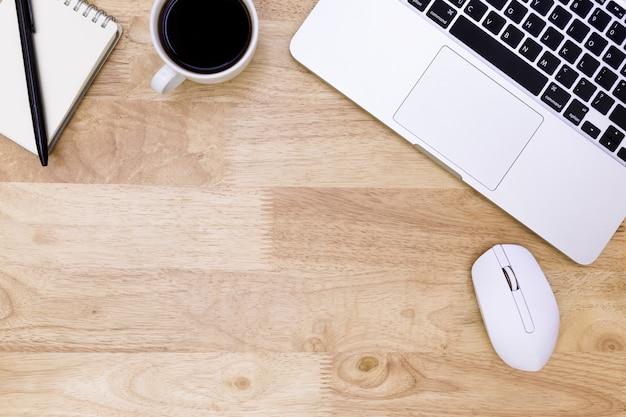 木製テーブル、ノートパソコンの背景にラップトップで現代の職場のフラットレイアウトオフィスデスクテーブル