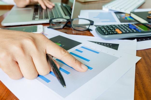 ビジネス会計計画コンセプト、ビジネスを行うための計算機とデスクトップラップトップコンピューターでの作業、