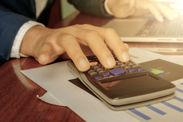ビジネス会計計画の概念、ビジネスを作るための電卓とデスクトップラップトップコンピューターで作業、木製デスクビジネス投資顧問のラップトップコンピューターで作業するビジネスの男の手。