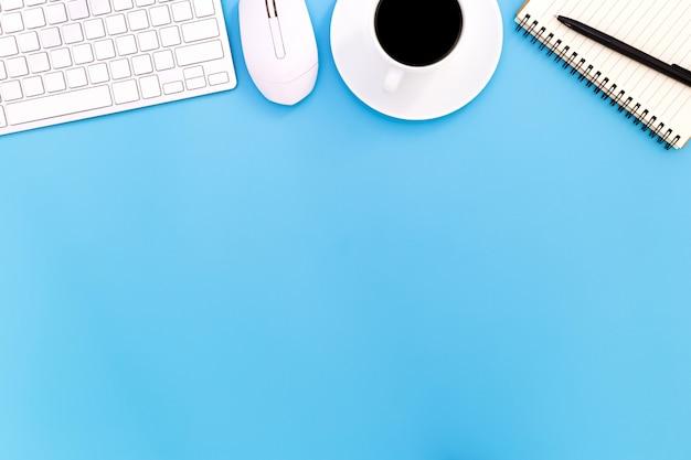 青いテーブルの上のラップトップ、トップビューのラップトップの背景と黒の背景にコピースペース、ラップトップと青いデスクオフィスと現代の職場のフラットレイアウトオフィスデスクテーブル、