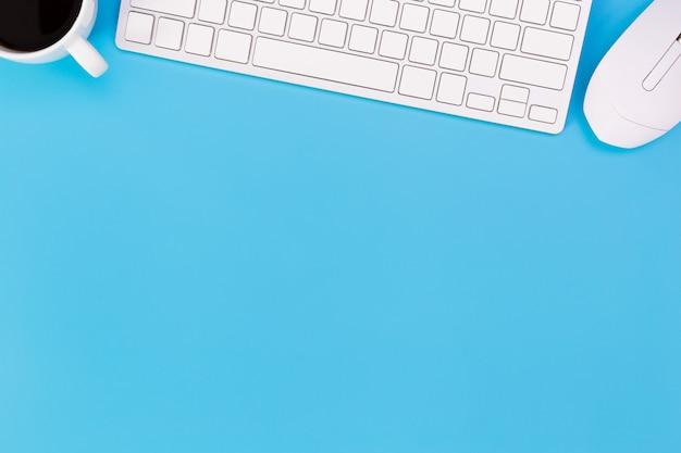 Плоский лежал офисный стол современного рабочего места с ноутбуком на синем столе,