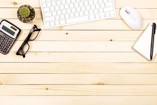 木製のテーブル、トップビューでノートパソコンと現代の職場のオフィスデスクテーブル