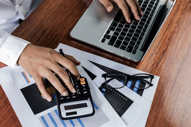 木製のテーブルのラップトップで現代の職場で働くビジネスマン、男は自宅からの仕事のためのラップトップのキーボードに手、