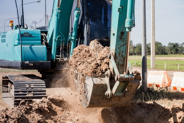 トレンチを掘る作業掘削機トラクター。