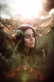バックライトとフレアを右見て隔離されたブッシュの目を閉じて若い美しい女性