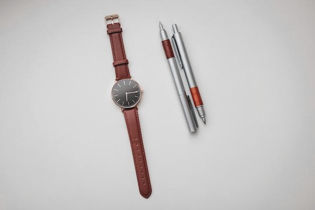 Высокая деталь угла обзора черно-коричневых наручных часов и пары коричневых и серебряных ручек на белом фоне.