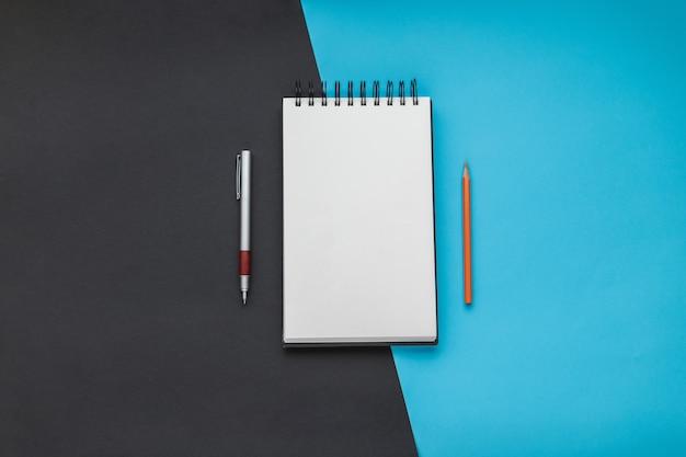 ペンと鉛筆でノートブックを開く