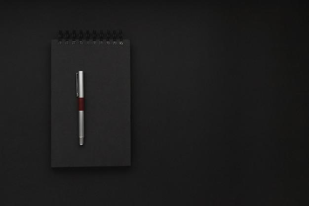 黒い背景の真ん中にその上に銀の派手なペンが付いた黒いスパイラルノート。シンプルな職場。