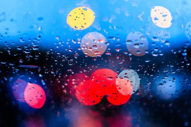 青いぼやけた交通上の車の窓に雨の滴