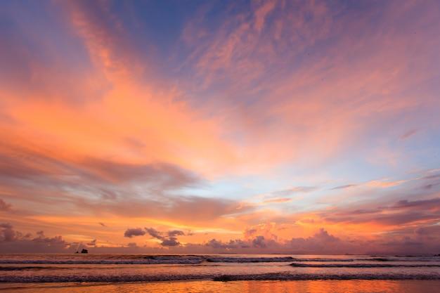 熱帯のビーチと島の美しい夕焼け空