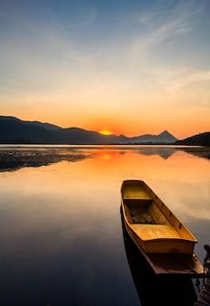 山と日の出の夕暮れの空と湖の小さな漁師のボート