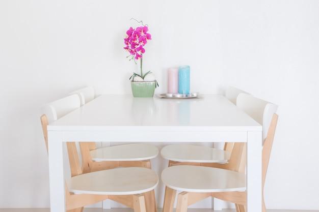 紫色の蘭の装飾が施された白いディナーテーブル