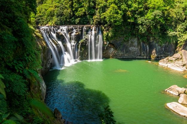 Красивый водопад в глубоком лесу.