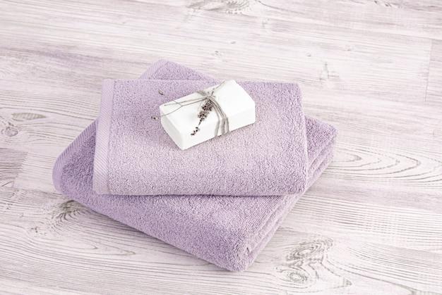 木製の背景に石鹸で折り畳まれ、積み重ねられたテリータオル