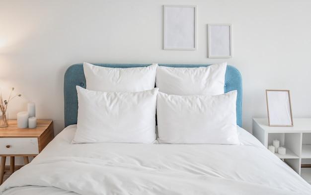 青い枕の上に白い枕と羽毛布団。