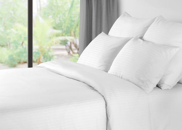 Кровать с бельем на фоне окна с серыми шторами