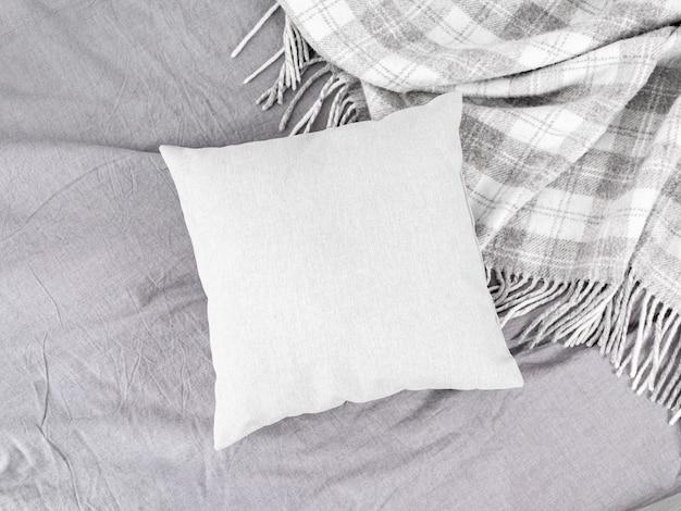 グレーのウールの格子縞またはキルト、クッション、グレーのベッドリネン付きのベッド