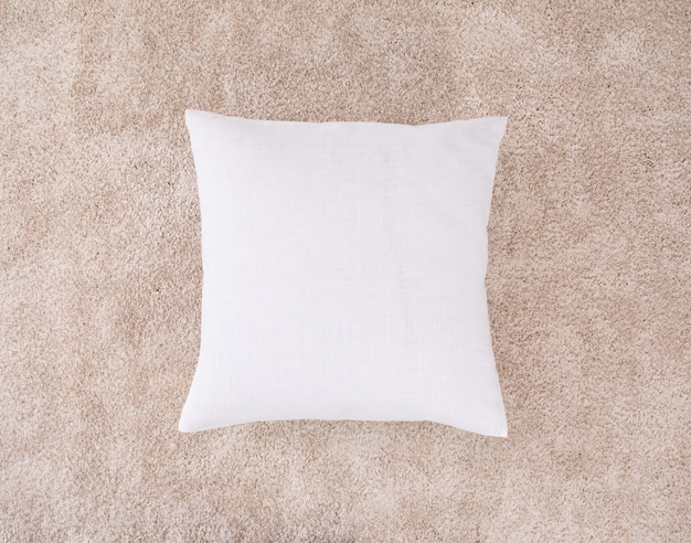 Белая подушка на коричневом коврике. одна подушка с чехлом.