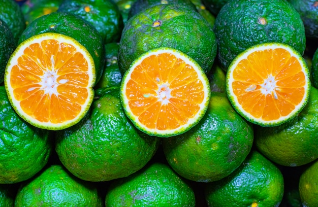 Куча зеленых апельсинов весь и нарезанный, вид сверху. половинки и целые зеленые апельсины.