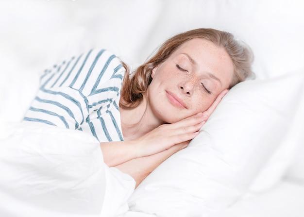 Молодая женщина спит в постели.