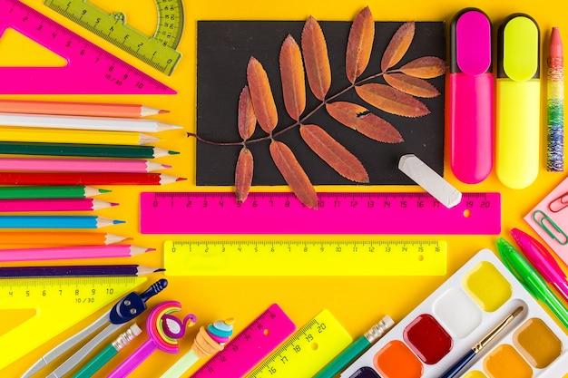 Школьные принадлежности и коричневый лист, вид сверху