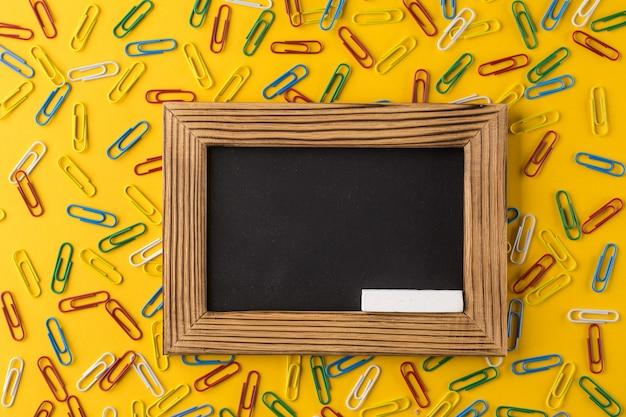 Скрепки и пустая рамка для фотографий