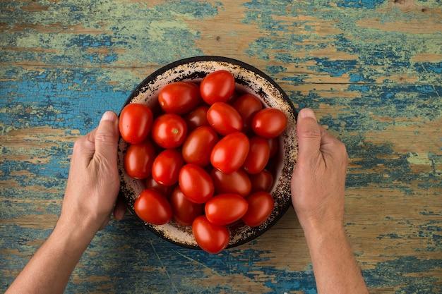 木製のテーブルの上の金属板で完熟トマト