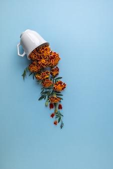 青にマリーゴールドの花とコーヒーまたは紅茶のカップ