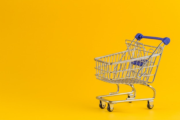 明るい黄色の紙の上のショッピングカート