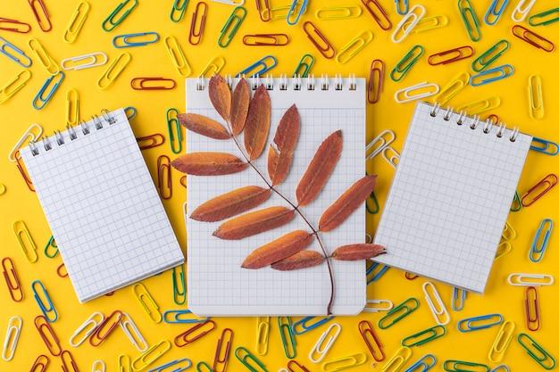 明るい黄色の紙の上のペーパークリップとメモ帳