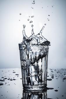 Закройте вверх по взгляду выплеска воды в граненном стекле.
