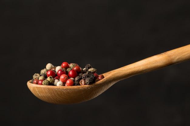 木のスプーンで色の唐辛子をクローズアップ
