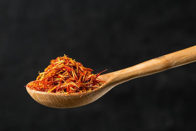 木のスプーンでサフラン調味料をクローズアップ