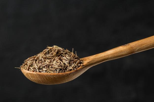 木のスプーンでクミン調味料をクローズアップ