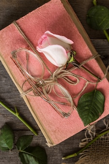 ビンテージスタイルの古い本にピンクのバラ