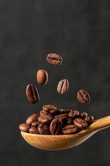 Макрос падающий кофе в зернах на сером фоне