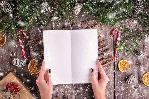 木の上のサンタさんへ手紙を書く女性の手