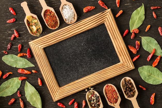 暗い石のテーブルにさまざまなスパイスのフレーム