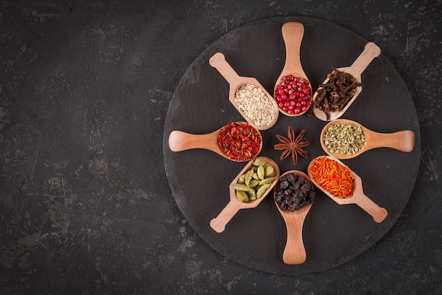 暗い石のテーブルに木製のスプーンで様々なスパイス。