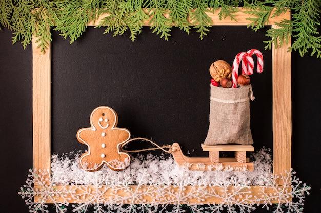 空の黒い黒板とクリスマスのジンジャーブレッドクッキー