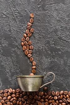 Кофе в зернах и кружка на сером фоне бетона