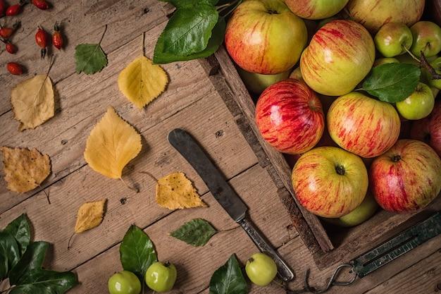 素朴なテーブルの上の緑と赤のリンゴ。トーン写真