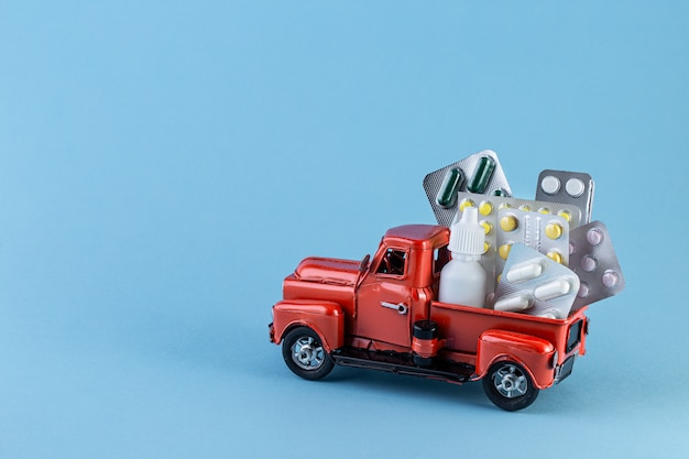 青色の背景に薬と一緒におもちゃの車のトラック。
