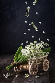 繊細な谷間のユリの花束。暗い背景に白い花を飛んでください。