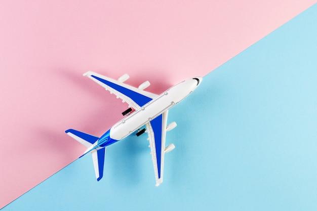 模型飛行機、ピンクとブルーの背景の飛行機。夏の旅行のコンセプト