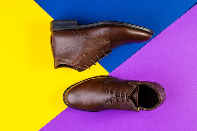 紙の背景の色に茶色の革のブーツのペア。