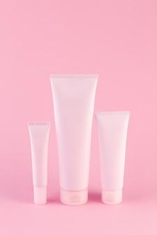 Коллекция из трех косметических трубок на пастельных розовом фоне.