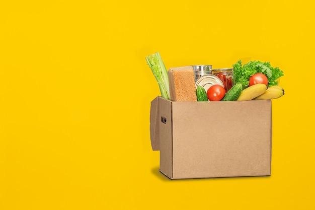 黄色の背景の上に食べ物が募金箱。コロナウイルスの食品配達