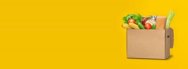 黄色の背景の上に食べ物が募金箱。コロナウイルスの食品配達。