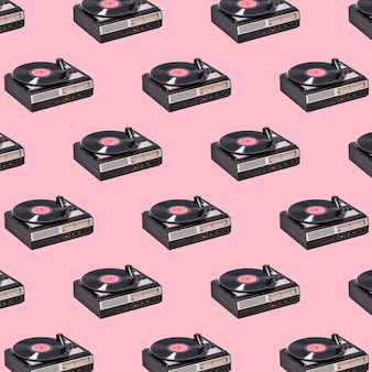 ビンテージビニールターンテーブルとピンクの背景のビニールレコード。レトロなサウンドテクノロジー。